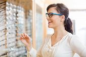 Happy young woman trying new glasses at optician store poster