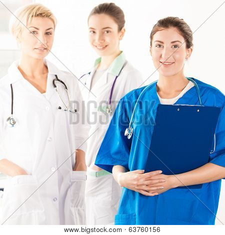 Smiling nurse with two doctors in hospital corridor