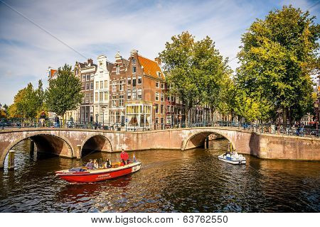 AMSTERDAM - SEPTEMBER 30, 2012: Boats on the canals in Amsterdam, Netherlands. Construction of the canal system started in Amsterdam in 1613 proceeding from west to east.