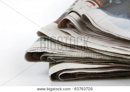 Pile of newspapers on plain background
