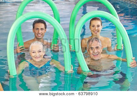 Group of senior people with swim noodles in a swimming pool
