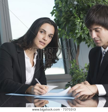 Young businesswoman signing some papers