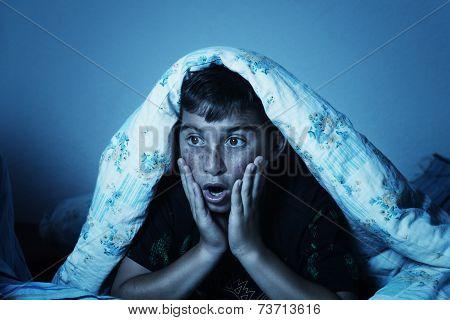 horrified boy watching film at night