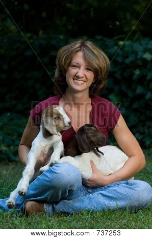 Outdoor portrait of a cute teenaged girl with her baby goats poster