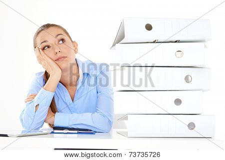 Bored female employee with a lot of work left to do on white background