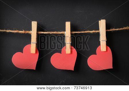 Three Hearts Hanging On Blackboard