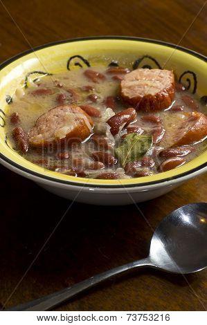 Polish sauerkraut kielbasa and bean soup with bay leaf garnish