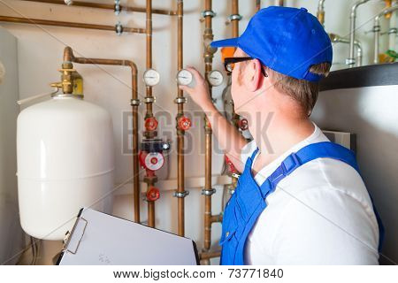 Engineer controlling the heating pipes at the boiler room