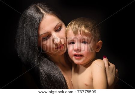 Crying child in mother's arms