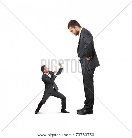 concept photo of conflict between subordinate and boss. scared small businessman waving his fists, displeased big man looking at him. isolated on white background
