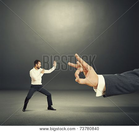 concept photo of conflict between subordinate and boss. angry young businessman ready for fight with big flick of his boss. photo in the dark room