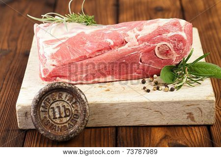 raw shoulder lamb on wooden board and table  with 1lb iron weight poster