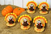 Homemade Thanksgiving turkey shaped cookies on burlap with pumpkins poster