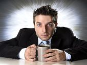 young addict businessman in suit and tie holding cup of coffee anxious and crazy in caffeine addiction and need to keep awaken on zoom effect grunge background poster