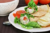 Healthy tuna salad wraps with a side of chips. Bowl of tomato soup and fresh tomatoes in the background. poster