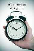 an alarm clock adjusting backward one hour and the text end of daylight saving time poster