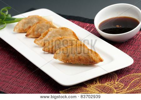 Fried thai gyoza dumpling appetizers with soy dipping sauce. poster