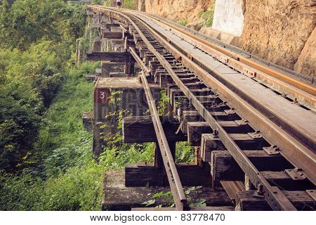 Railroad tracks through a forest, mountain and countryside, Thailand.