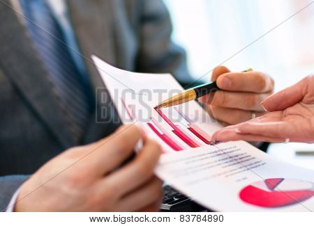 Image of human hand pointing at paper during explanation
