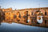 Roman bridge of Merida, UNESCO site, sunset and reflections in the river poster