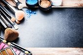 Various makeup products on dark background with copyspace poster