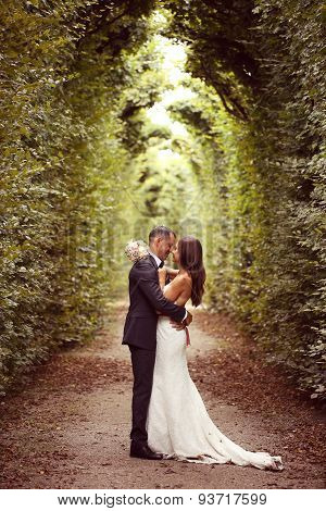 Vertical photograph of a bride and groom embracing surrounded by trees poster
