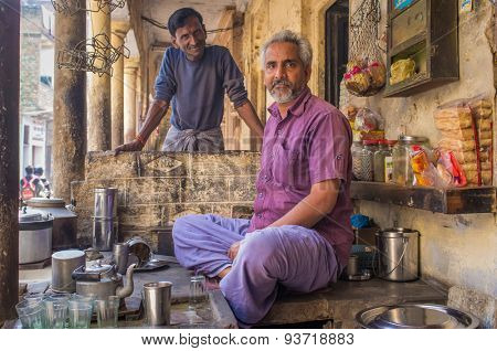 VARANASI, INDIA - 21 FEBRUARY 2015: Street vendor selling milky tea, called chai,  sits in shop while neighbouring carpenter stands behind.