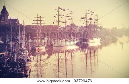 Retro Toned Photo Of Sailing Ships At Sunrise.
