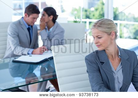 Businesswoman whispering something to her colleague in an office