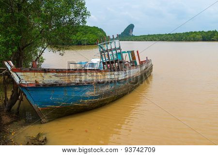 Old Wooden Boat, Abandoned And Deteriorating On A Muddy River