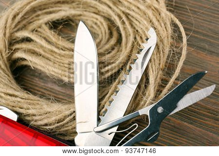 Pocket knife with rope on wooden table close up