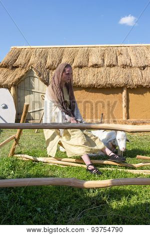 Shepherdess Tending A Goat In The Backyard Of A Clay Hut