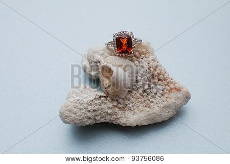 Orange citrine gold engagement ring on a shell and coral reef