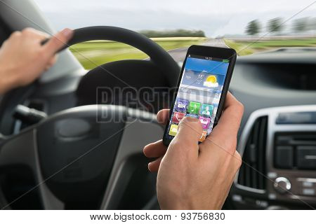 Person's Hand Using Cellphone While Driving A Car