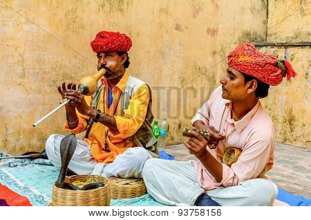 Snake charmer playing flute for the snake