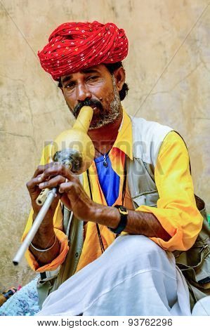 Jaipur, India- March 12, 2015:: A Snake Charmer Is Playing The Flute For The Cobra Sitting B The Wal