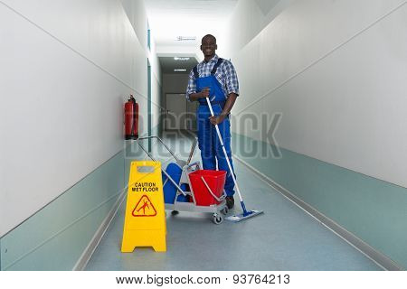 Janitor Holding Mop With Bucket And Wet Floor Sign