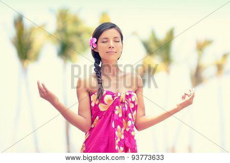 Serene meditation. Woman meditating on Hawaiian palm beach in sarong, hands up. Beautiful biracial female model enjoying sun in worship and meditation zen. Big Island, Hawaii, USA.