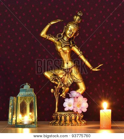 Bronze statue illuminated by candles