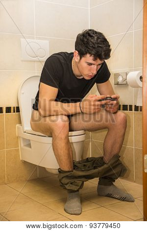 Young Man with Cell Phone Sitting on Toilet