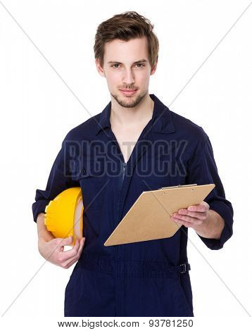 Construction site worker with protective hat and clipboard