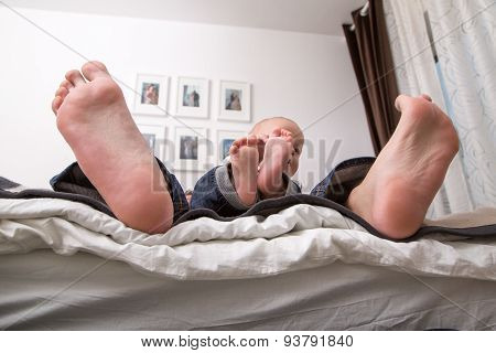 Child Playing With The Big Toe Of His Father