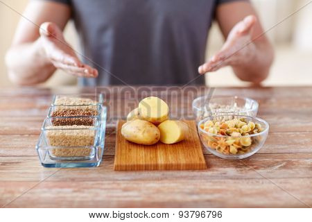 healthy eating, diet and people concept - close up of male hands showing carbohydrate food on table
