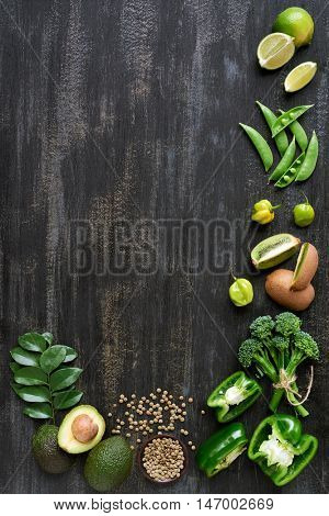Food poster collection of fresh green vegetables on dark rustic distressed background,  limes, capsicum, peppers, peas,  kiwi, cucumber, habanero, lentils