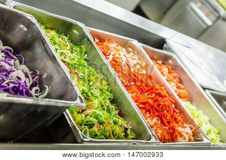 Stainless steel bins of chopped lettuce and sliced red peppers