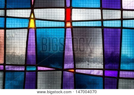 Close-crop section of abstract stained glass detail in tones of blue, turquoise and purple.