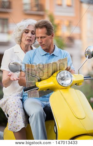 Mature couple on yellow scooter. Man and woman with map. Which way is best. Getting lost on the way.