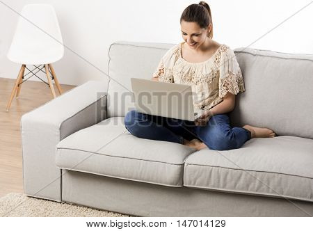 Beautiful woman at home working on her laptop