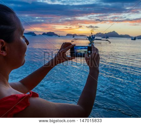Woman taking pictures with her smartphone at sunset on tropical beach