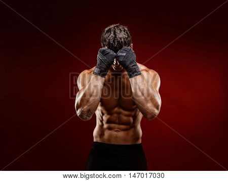 Unrecognizable topless man in fighting gloves covering face with fists on red background. Isolate.
